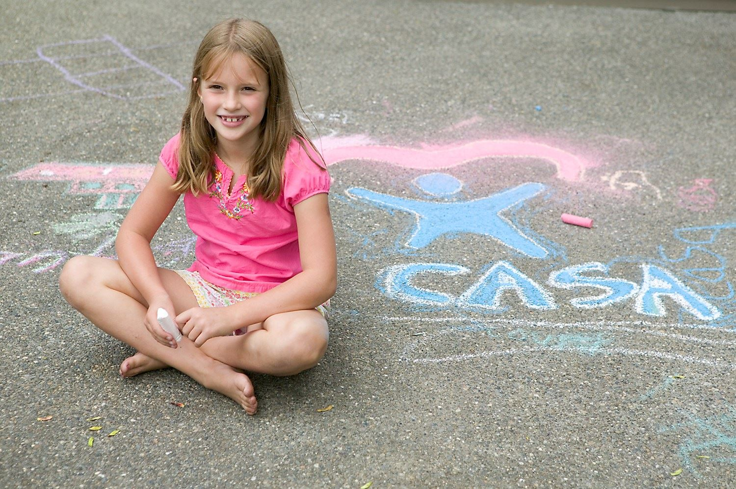 Girl Sitting on Pavement with Chalk Drawing of CASA